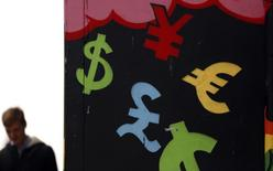 Символы различных валют на стене в Дублине 22 октября 2014 года. Доллар растет к иене накануне публикации экономической статистики США и Китая, а австралийский доллар дешевеет, потому что центробанк Австралии не исключает возможности интервенций. REUTERS/Cathal McNaughton