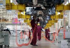 Рабочие на автомобильном заводе в городе Хефей, КНР 15 марта 2014 года. Экономика Китая снова сбавила темпы в октябре: рост промышленного производства остался на минимальных значениях, а рост инвестиций достиг почти 13-летнего минимума, подтверждая, что Пекину придется принять меры, чтобы поддержать слабеющую экономику. REUTERS/Stringer