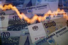 График колебания курса рубля к доллару на фоне рублевых купюр в Варшаве 7 ноября 2014 года. Рубль в минусе на полуденных торгах четверга, отражая падение нефти к новым многолетним минимумам. REUTERS/Kacper Pempel