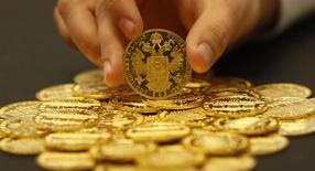 Золотые монеты в австрийском аукционном доме Dorotheum в Вене 16 апреля 2013 года. Цены на золото стабильны, пока инвесторы ждут еженедельный отчет о числе обращений за пособием по безработице в США. REUTERS/Leonhard Foeger