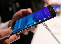 Le Note Edge de Samsung vendu en Corée (à près de 1.000 dollars), au Japon et bientôt aux Etats-Unis.  Les écrans courbes pourraient être l'une des clés du rétablissement de la domination de Samsung Electronics sur le marché des téléphones multimédias, grâce à des smartphones haut-de-gamme difficilement imitables.  /Photo prise le 3 septembre 2014/REUTERS/Hannibal Hanschke