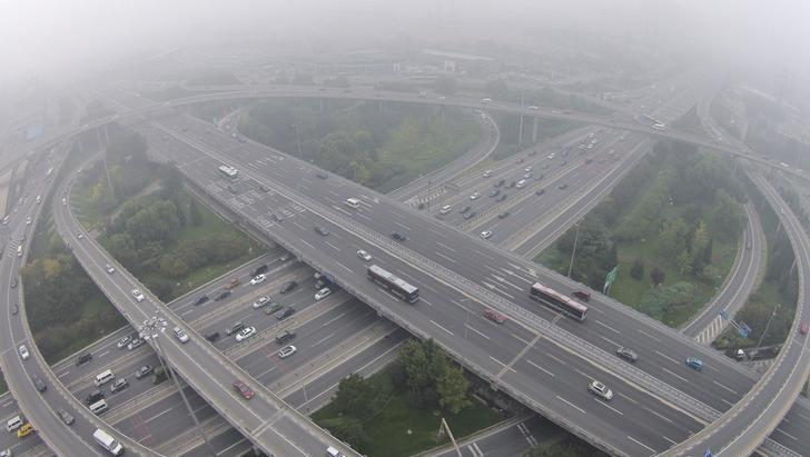 Vehicles drive on the Sihui overpass amid heavy haze and smog in Beijing, October 11, 2014. REUTERS/Jason Lee