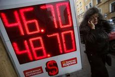 Экран с курсами обмена валют в Санкт-Петербурге 7 ноября 2014 года. Рубль резко подешевел при открытии торгов пятницы на фоне падения нефти на новые многолетние минимумы и в условиях высоковолатильного свободного плавания и тонкого рынка после отмены Центробанком валютного коридора и регулярных интервенций. REUTERS/Alexander Demianchuk