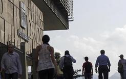 Personas pasan frente a la sede de la brasileña Petrobras en Rio de Janeiro. Imagen de archivo, 11 abril, 2014.  La policía federal de Brasil ordenó el viernes 27 arrestos adicionales como parte de una investigación por lavado de dinero que ha involucrado a un ex importante ejecutivo de la petrolera estatal Petrobras, lo que ha causado una demora en la difusión de los resultados financieros de la empresa. REUTERS/Ricardo Moraes