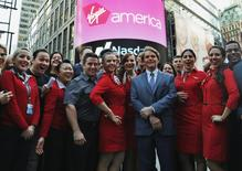 Virgin America Inc. President and Chief Executive Officer David Cush (3rd R) poses for photographs with Virgin America flight crews as Virgin America Inc. celebrated its initial public offering at the NASDAQ Market Site in New York, November 14, 2014. REUTERS/Mike Segar