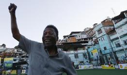 Pelé posa para la prensa en la inauguración de un campo de fútbol en la barriada Mineira de Rio de Janeiro, en una fotografía de archivo. 10 de septiembre de 2014. El ex astro del fútbol fue dado de alta el sábado de un hospital de Sao Paulo tras haber sido sometido a un procedimiento quirúrgico para retirarle unos cálculos, informaron los médicos. REUTERS/Ricardo Moraes