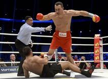 Ukrainian WBA, WBO, IBO and IBF heavyweight boxing world champion Vladimir Klitschko knocks down his challenger Bulgarian Kubrat Pulev during their title fight in Hamburg, November 15, 2014.     REUTERS/Fabian Bimmer