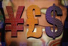 The dollar sign (R) is seen alongside the signs for other currencies above a currency exchange shop in Mongkok shopping district in Hong Kong October 30, 2014. REUTERS/Damir Sagolj