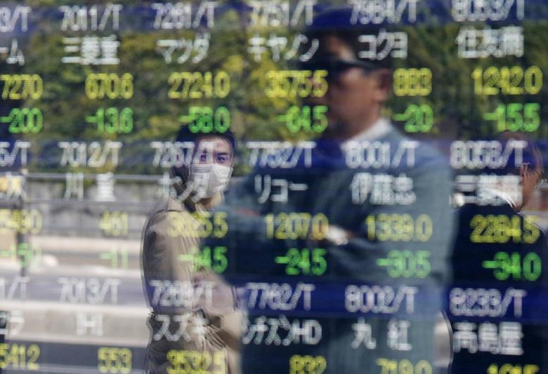 Passers-by are reflected on an electronic stock quotation board outside a brokerage in Tokyo, November 17, 2014. REUTERS/Issei Kato