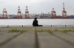 Бизнесмен сидит на набережной напротив грузового терминала порта Токио 19 апреля 2012 года. Экономика Японии неожиданно скатилась в рецессию в третьем квартале, что добавляет поводов премьер-министру Синдзо Абэ отложить повышение налога с продаж и провести досрочные выборы. REUTERS/Toru Hanai