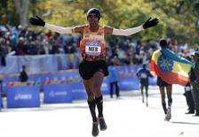 Meb Keflezighi of USA (L) runs for the finish line to finish fourth in the men's professional division of the 2014 New York City Marathon in Central Park in Manhattan, November 2, 2014.  REUTERS/Mike Segar
