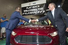 Joe Hinrichs, Ford's president of the Americas (R) and Jimmy Settles, UAW vice president of the National Ford Department, shake hands over the first 2014 Fusion produced in the United States during a news event to announce the beginning of Ford Fusion production at the assembly plant in Flat Rock, Michigan August 29, 2013.  REUTERS/James Fassinger