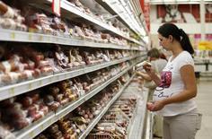 Покупатели в колбасном отделе магазина Ашан в Москве 18 августа 2014 года. Чистая прибыль одного из крупнейших российских мясопереработчиков группы Черкизово в третьем квартале 2014 года выросла в восемь к аналогичному периоду предыдущего года до $112,8 миллиона благодаря высоким ценам. REUTERS/Maxim Zmeyev