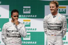 Second placed Mercedes Formula One driver Lewis Hamilton (L) of Britain reacts near next to winner Mercedes Formula One driver Nico Rosberg of Germany, during the podium ceremony after the Brazilian Grand Prix in Sao Paulo November 9, 2014. REUTERS/Paulo Whitaker