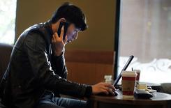 Un hombre habla por su teléfono mientras navega en internet con su laptop en una cafetería en Shanghai. Imagen de archivo, 28 noviembre, 2014. Funcionarios chinos llamaron el miércoles al establecimiento de controles sobre Internet para preservar la estabilidad y dijeron que su modelo para la regulación del ciberespacio puede ser el marco para dar origen a éxitos comerciales como Alibaba Group Holding Ltd.  REUTERS/Carlos Barria