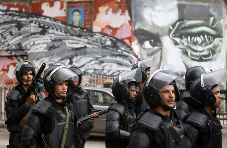 Riot police walk in front of graffiti depicting Bassem Mohsen, 20, who was killed in the 2011 Egypt uprising, along Mohamed Mahmoud street  during the third anniversary of violent and deadly clashes near Tahrir Square in Cairo November 19, 2014. REUTERS/Amr Abdallah Dalsh