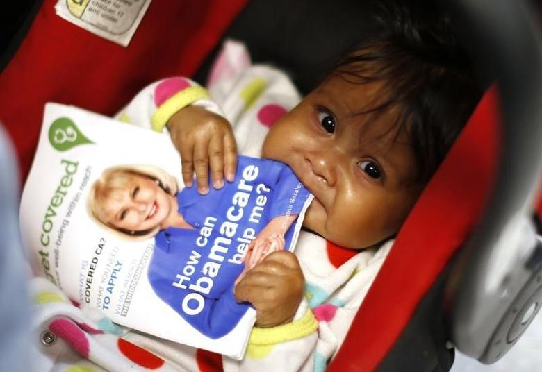 Six-month-old Hazel Garcia chews a pamphlet at a health insurance enrollment event in Cudahy, California March 27, 2014.   REUTERS/Lucy Nicholson