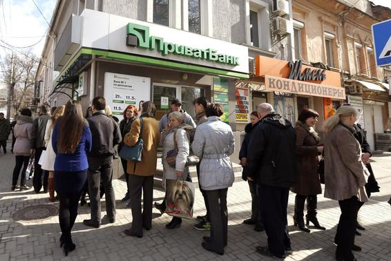 People stand in line to withdraw money at an automated teller machine (ATM) of Ukrainian bank Privatbank in Simferopol, in this March 14, 2014 file photo.  REUTERS-Vasily Fedosenko-Files
