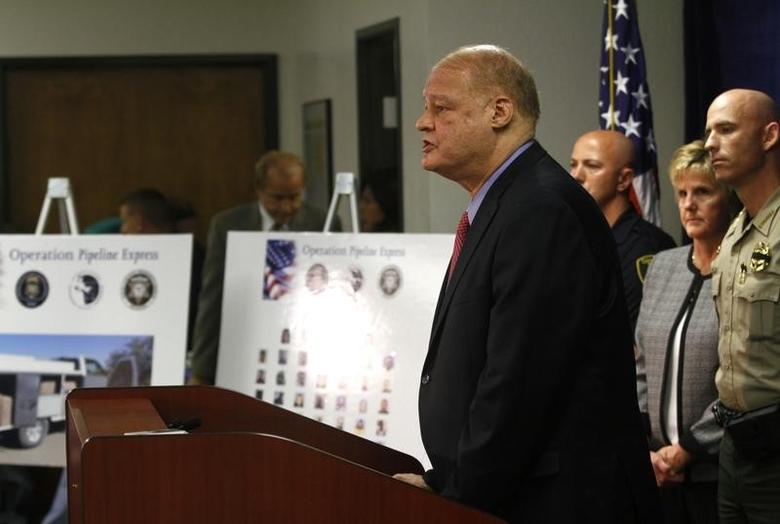 Pinal County Sheriff Paul Babeu (R) listens as Arizona Attorney General Tom Horne speaks about weapons and drugs seized from the Mexican Sinaloa cartel during ''Operation Pipeline Express'' at a news conference in Phoenix, Arizona October 31, 2011. REUTERS/Joshua Lott