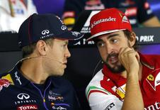 Red Bull Formula One driver Sebastian Vettel (L) of Germany talks with Ferrari Formula One driver Fernando Alonso of Spain during a news conference ahead of the Russian Grand Prix in the Sochi Autodrom circuit October 9, 2014. REUTERS/Laszlo Balogh