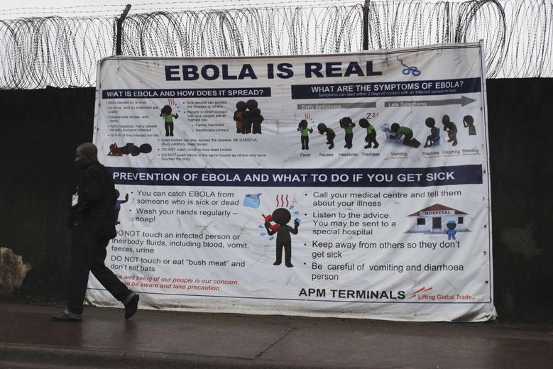 A man walks by a sign that reads ''Ebola is real'' in Monrovia, Liberia, October 21, 2014. REUTERS/James Giahyue/Files