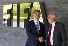 Michael J. Garcia, Chairman of the investigatory chamber of the FIFA Ethics Committee (L) and Hans-Joachim Eckert, Chairman of the adjudicatory chamber of the FIFA Ethics Committee shake hands as they pose for photographers after a news conference at the at the Home of FIFA in Zurich July 27, 2012 REUTERS/Michael Buholzer