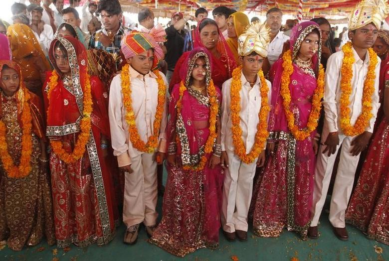 Boys and girls from the Saraniya community wearing garlands pose for pictures after their engagement ceremony at Vadia village in Gujarat March 11, 2012. REUTERS/Amit Dave/Files