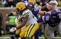 Nov 23, 2014; Minneapolis, MN, USA; Green Bay Packers running back Eddie Lacy (27) is tackled by Minnesota Vikings linebacker Chad Greenway (52) and defensive tackle Linval Joseph (98) during the third quarter at TCF Bank Stadium. The Packers defeated the Vikings 24-21. Mandatory Credit: Brace Hemmelgarn-USA TODAY Sports