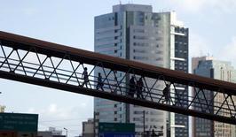 Personas caminan por un puente peatonal en Salvador. Imagen de archivo, 11 junio, 2014. Los economistas elevaron sus pronósticos para la tasa de inflación de Brasil a fines del 2014 y del 2015 a 6,43 por ciento y 6,45 por ciento, respectivamente, mostró el lunes el sondeo semanal Focus del Banco Central. REUTERS/Marcos Brindicci