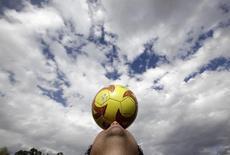 """Болельщик мексиканского футбольного клуба """"Америка"""" удерживает мяч на голове у стадиона """"Ацтека"""" в Мехико 31 января 2010 года. REUTERS/Daniel Aguilar"""