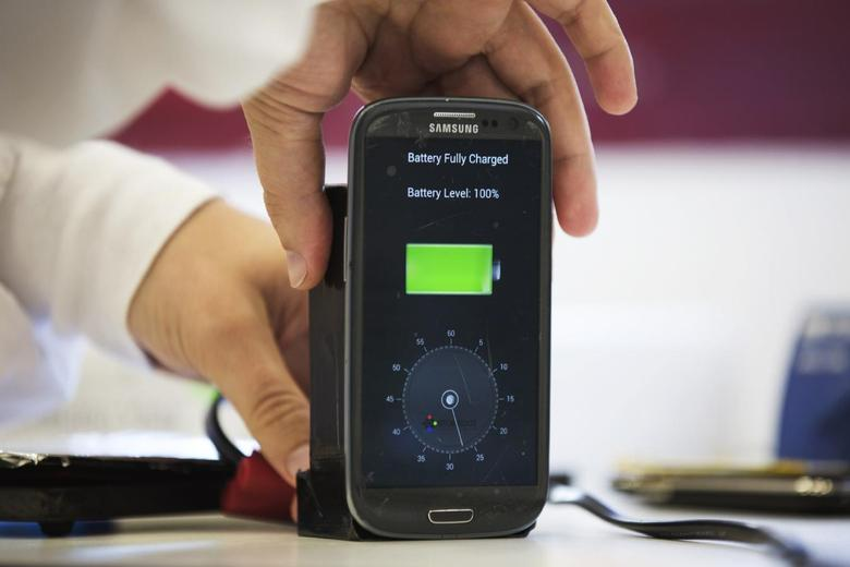 A lab worker disconnects from a charger a mobile phone, displaying a timer indicating that the battery was fully charged under 30 seconds, at the headquarters of StoreDot in Tel Aviv October 23, 2014. REUTERS/Finbarr O'Reilly