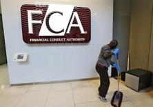 A maintenance worker cleans the entrance area of the headquarters of the new Financial Conduct Authority (FCA) in the Canary Wharf business district of London in this April 1, 2013 file photo. REUTERS/Chris Helgren/Files