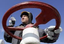 Сотрудник Роснефти на объекте Юганскнефтегаза близ Нефтеюганска 26 апреля 2006 года. РФ не собирается снижать добычу нефти в 2015 году, несмотря на низкие цены из-за избытка предложения, но будет наблюдать за ситуацией на мировом рынке, сказал министр энергетики Александр Новак. REUTERS/Sergei Karpukhin