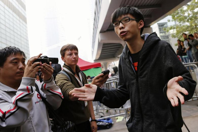 Joshua Wong (R), a student leader from Scholarism, speaks to reporters as he and other protesters wait for the arrival of bailiffs under court injunction to clear up part of the protest site, outside the government headquarters in Hong Kong November 18, 2014. REUTERS/Tyrone Siu