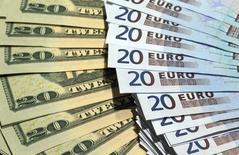 Billetes de dólares americanos y euros vistos en una fotografía tomada en París. Imagen de archivo, 28 octubre, 2014. El euro caía el jueves frente al dólar tras conocerse que la inflación en Alemania parecía haberse debilitado más en noviembre, reforzando las expectativas de que el Banco Central Europeo suavice su política monetaria de forma más agresiva. REUTERS/Philippe Wojazer