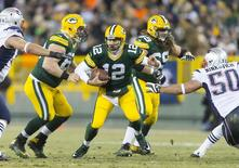 Green Bay Packers quarterback Aaron Rodgers (12) scrambles with the football during the third quarter against the New England Patriots at Lambeau Field.  Green Bay won 26-21.  Mandatory Credit: Jeff Hanisch-USA TODAY Sports