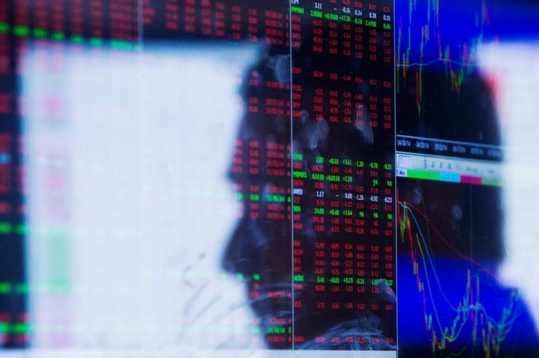 The face of a trader is reflected on the screen of a terminal on the floor of the New York Stock Exchange, September 29, 2014. REUTERS/Lucas Jackson