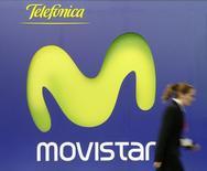 Imagen de archivo de una mujer pasando frente al logo de Movistar en Barcelona. 15 febrero, 2007. Argentina adjudicó el martes frecuencias de telefonía móvil de cuarta generación (4G) a la empresa Movistar, controlada por la española Telefónica, por 209 millones de dólares, en el marco de una licitación pública por la que el país recibió también ofertas de otras tres firmas. REUTERS/Albert Gea