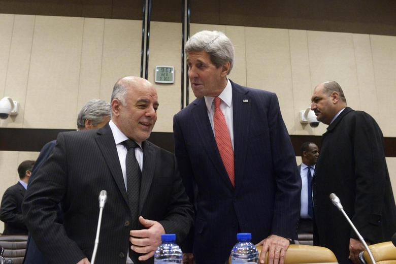 Iraqi Prime Minister Haider al-Abadi (L) speaks to U.S. Secretary of State John Kerry prior to a round table meeting of the global coalition to counter the Islamic State militant group at NATO headquarters in Brussels December 3, 2014.       REUTERS/Eric Vidal