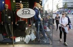Unas personas pasan frente a una tienda comercial en Montevideo, ago 20 2014. Los precios minoristas de Uruguay avanzaron un 0,15 por ciento en noviembre, casi la mitad de lo estimado por el mercado, en un mes en el que subieron los costos en vivienda, vestimenta y servicios, informó el miércoles el Gobierno.   REUTERS/Andres Stapff