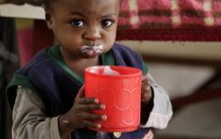 Un niño bebe leche dentro de un centro comunitario en Goma, región de North Kivu. Imagen de archivo, 6 agosto, 2013.  Los precios mundiales de los alimentos se mantuvieron estables en noviembre por tercer mes consecutivo debido a que mayores costos de los cereales y de los aceites vegetales fueron contrarrestados por caídas del azúcar y los productos lácteos, dijo el jueves la agencia de alimentos de Naciones Unidas. REUTERS/Thomas Mukoya