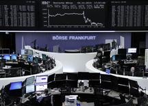 Traders are pictured at their desks in front of the German share price index DAX board at the Frankfurt stock exchange December 4, 2014. REUTERS/Remote/Stringer