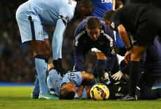 Yaya Toure stands over Sergio Aguero of Manchester City as he reacts after sustaining an injury during their English Premier League soccer match against Everton at the Etihad Stadium in Manchester, December 6, 2014.    REUTERS/Darren Staples