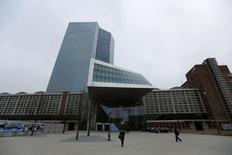 People walk past the new ECB headquarters in Frankfurt December 4, 2014. REUTERS/Kai Pfaffenbach