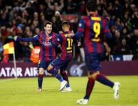 Barcelona's Lionel Messi (L) celebrates with team mates Neymar and Luis Suarez (R) after scoring his second goal against Espanyol during their Spanish first division soccer match at Nou Camp stadium in Barcelona December 7, 2014.  REUTERS/Gustau Nacarino