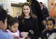 Kate Middleton, the Duchess of Cambridge, laughs while siting next to April, 4, (L), and Sammy, 4, in a pre-school class at the Northside Center for Childhood Development in New York, December 8, 2014. REUTER/Seth Wenig/Pool