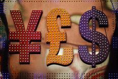 Символы иены, фунта и доллара у пункта обмена валюты в Гонконге 30 октября 2014 года. Курс иены растет, так как инвесторы не хотят рисковать, видя падение цен на нефть. REUTERS/Damir Sagolj
