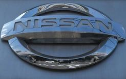 Cars are reflected in a Nissan Motor logo at the company's dealership in Tokyo July 28, 2014. REUTERS/Toru Hanai