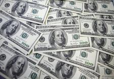 Долларовые купюры в банке в Сеуле 20 сентября 2011 года. Российская экономика потеряла несколько десятков миллиардов долларов от санкций Запада в ответ за аннексию Крыма и вмешательство в дела Украины, сказал премьер Дмитрий Медведев. REUTERS/Lee Jae-Won
