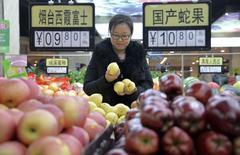 A Cliente elige fruta en un supermercado en Fuyang, provincia de Anhui, 10 dic, 2014. La inflación del consumidor en China se ralentizó en noviembre a un mínimo de cinco años de 1,4 por ciento interanual, desde un 1,6 por ciento en octubre, lo que indica una persistente debilidad de la segunda mayor economía mundial y brinda a las autoridades más razones para relajar su política monetaria. REUTERS/Stringer